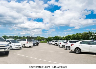 Car parking in large asphalt parking lot with trees line, white cloud and blue sky background in sunny day. Outdoor parking lot with fresh ozone and green environment of transportation and technology
