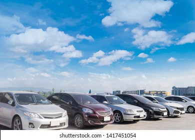 Car parking in large asphalt parking lot with white cloud and blue sky background in front of hall building. Outdoor parking lot with fresh ozone and green environment concept