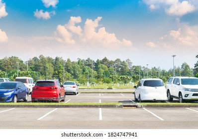 Car parking lot with car parked, cloud and blue sky background. Outdoor parking lot with fresh ozone and green environment of travel transportation technology concept