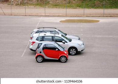 Car parking. Small red car is standing next to large cars.