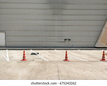 car parking lot with white mark and traffic orange cone on street.