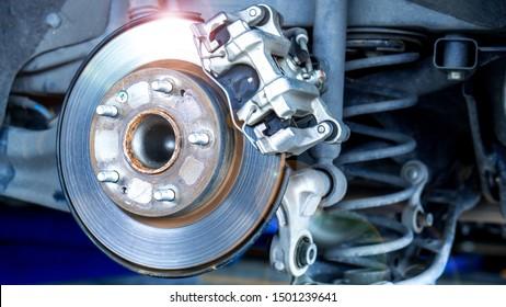 Car parts and disk brake concept - Closeup car disk brake maintenance service in car garage and copy spcae
