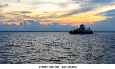 Car passenger ferry ship sailing out of port Labuan island,Malaysia during sunset.