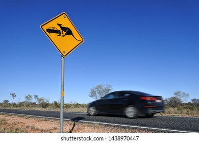 Car passing fast by a beware of the kangaroo road sign on Stuart highway in central Australia outback