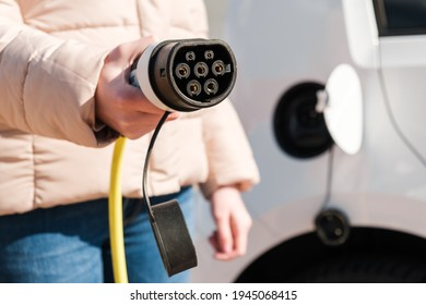 Car power charger in woman hand. Power supply for recharging of electric or EV car