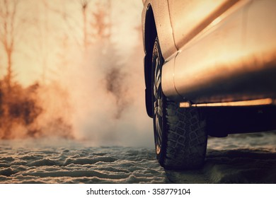 Car and powerful exhaust fumes in the air. The sun reflects light from the side of the car in the winter in Finland. Image includes a vintage effect.