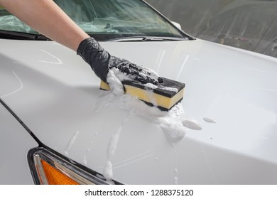 Car in the process of manual car wash with a yellow sponge and foam