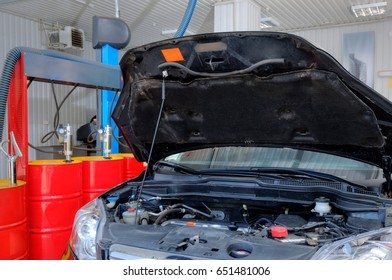 A car in a professional auto repair shop with hood up