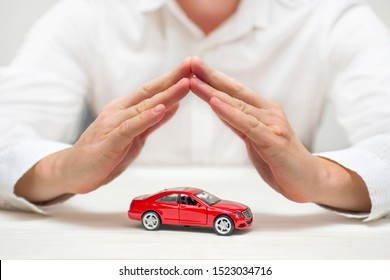 Car protection. Small red car covered by man hands. Car (automobile) insurance and collision damage waiver concepts.
