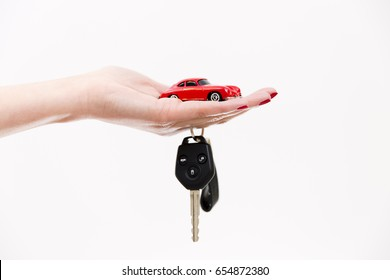 Car purchase concept. Toy car on woman's palm, car keys on finger