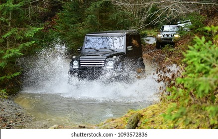 Car racing with creek on way. Extreme driving, competition and 4x4 vehicles concept. Offroad race in forest. SUV or offroad cars crossing water stream