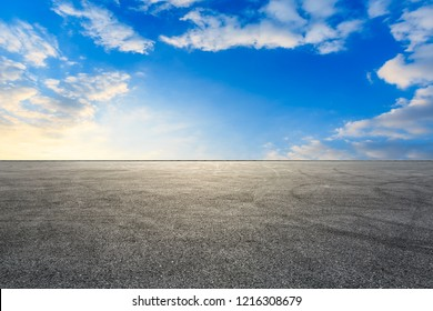 Car racing track asphalt square pavement and beautiful sky clouds scenery at sunset