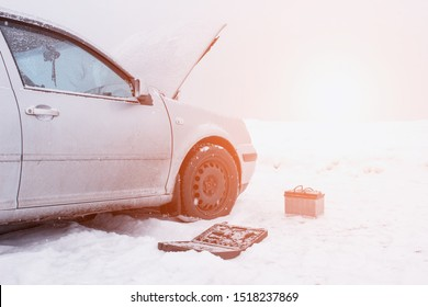 A car with a raised hood on a background of a snowy field, tools and a discharged car battery near the car, the concept of a car breakdown in winter