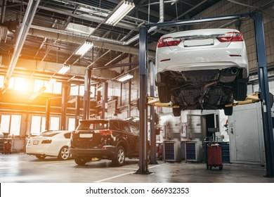 Автомобиль поднят на автоподъемнике в автосервисе.