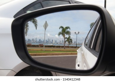 car rearview mirror where you can see beautiful view of the coast and city