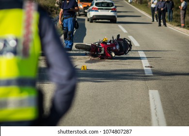 Car and a red sport motorcycle crash scene on an open road in afternoon. Workers and police seen around the crash site, with a queue of traffic building behind. Destroyed van and motorcycle.