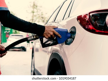 Car refuel in gas station : Selective focus on hand holding nozzle