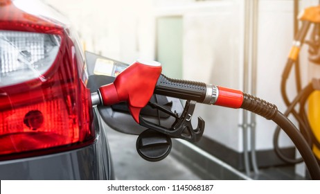 Car refueling  at gas station.With Red Fuel Nozzle