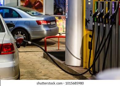 Car refueling on a petrol station at night closeup