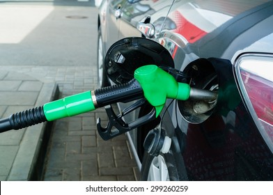 Car refueling on a petrol station. Focus on filling nozzles