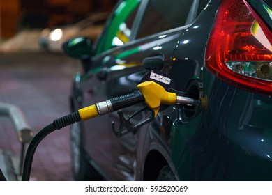 Car refueling on a petrol station at night closeup