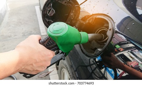Car refueling on petrol station, hand pumping gasoline oil.