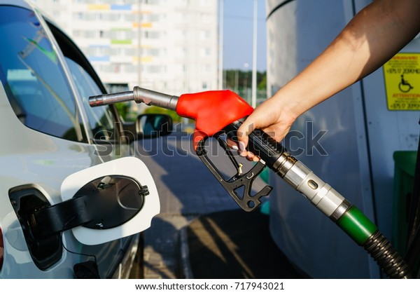 Car refueling on petrol station. Woman pumping gasoline oil