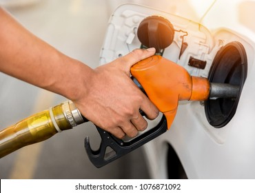 Car refueling on petrol station.staff pumping gasoline oil or handle fuel nozzle put in to tank of vehicle in warm sunset,transportation concept.