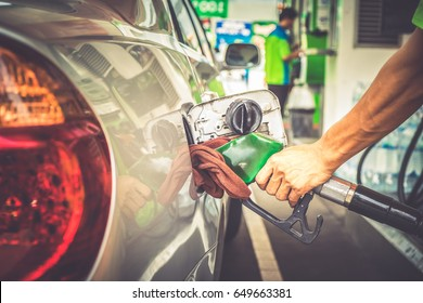 Car refueling in tank on petrol station. Man pumping gasoline oil. This photo can be used for fuel industry or transportation concept
