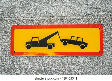 Car removal sign in yellow and red on a concrete wall