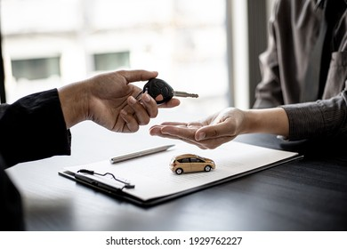 A car rental company employee is handing out the car keys to the renter after discussing the rental details and conditions together with the renter signing a car rental agreement. Concept car rental.
