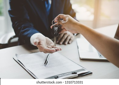 Car rental service concept. Close up view Hand of agent giving car key to customer after signed rental contract form.