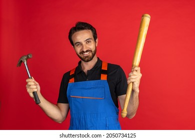 Car repair. Smiling young bearded man, male auto mechanic or fitter wearing blue work dungarees isolated over red studio background. Concept of funny meme emotions, ad, job, insipation, ideas, sales