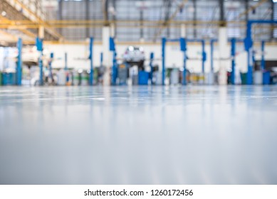 Car repair station paved with epoxy floor And a picture of an electric lift for a car that comes to change the engine oil in the background of an industrial plant with epoxy floors.