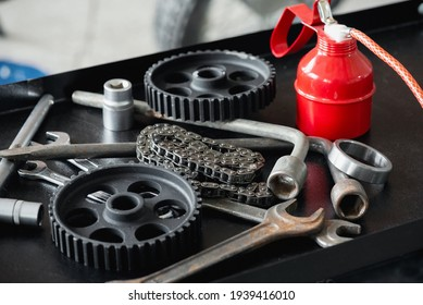 Car repairing service concept background. An old car spare parts, wrenches and red oil can on the metal workbench close up background.