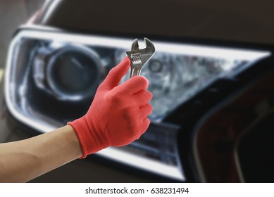 Car repairing,Hand of car technician auto mechanic with a wrench working in garage. service in auto repair station.vintage tone,for banner