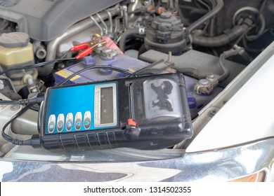 Car repairman take care of your car. Technicial check batery and cleaning engine.