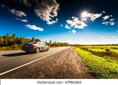 Car rides along the forest road which is in the field with haystacks lit by the sun on a blue sky background. High contrast and obscured image