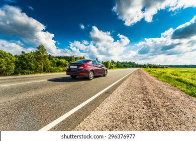 Car rides on a rural road that runs through the fields and forests