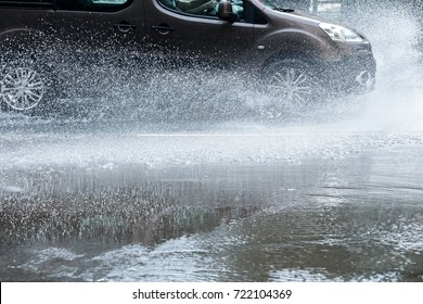 car rides through rain puddles on a wet street with splashing water
