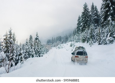the car is riding on the snow road in the mountains with high trees