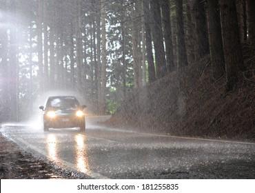 Car riding under heavy rainfall.