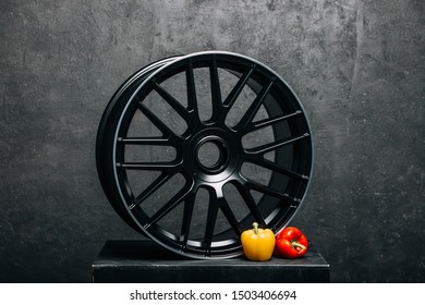 Car rims at the dark background with yellow pepper close up