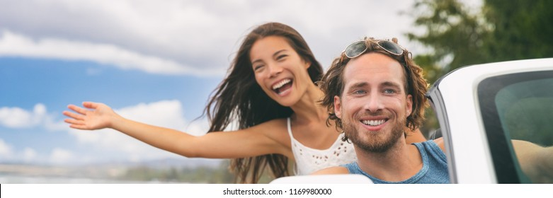 Car road trip travel fun young couple driving on summer vacation freedom banner. Happy free people in convertible cabriolet. Asian woman carefree with open arms joyful. Friends going on road trip.