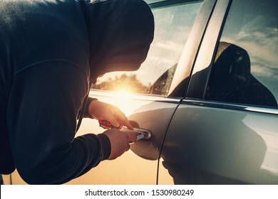 Car robber or thief trying to break auto door lock, close up. Car theft concept.