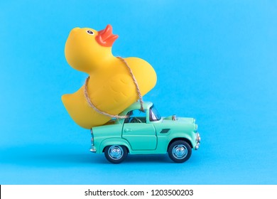 Car and rubber duck on blue background summer vacation minimal creative concept.
