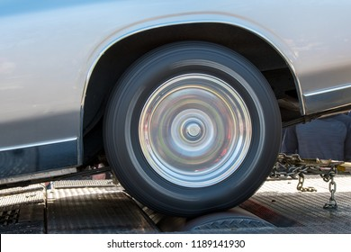 A car running at full speed on a dynamometer. The car is not moving but the wheel is spinning full speed. Closeup side view, in the shadows outdoors.