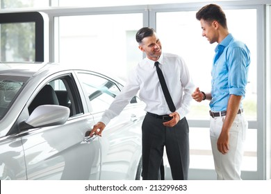 Car Sales Consultant Showing a New Car to a Potential Buyer in Showroom