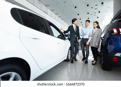 Car Sales Manager Showing Luxury Auto To Young Family Buyers In Automobile Dealership Store