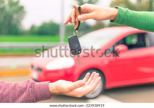 car sales. one person sells car and gives the key to the new owner